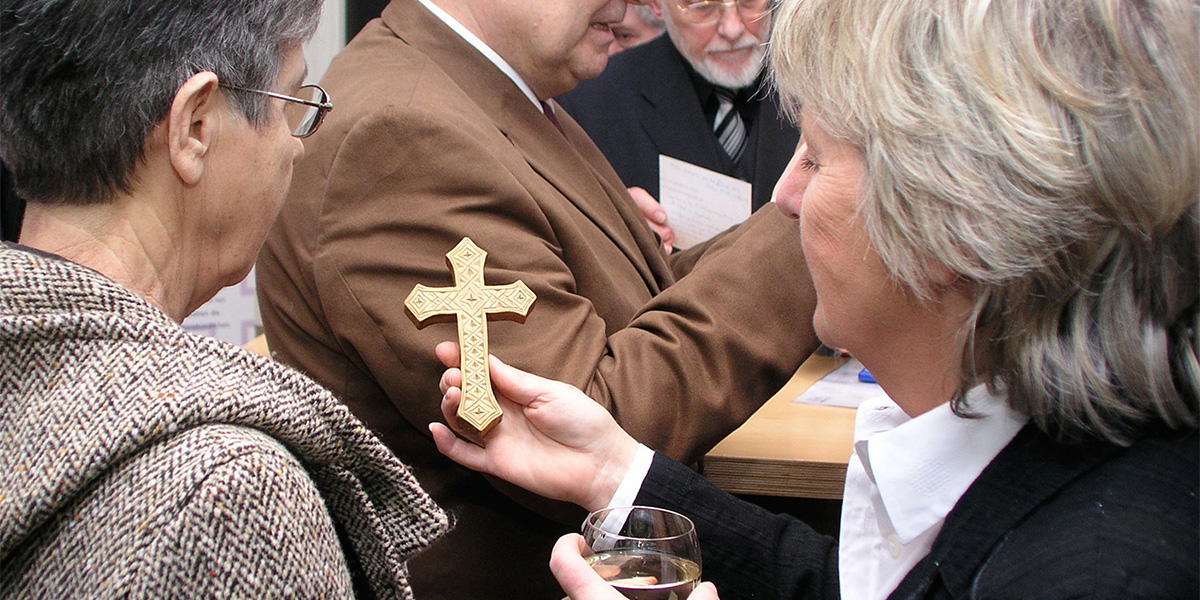zwei Frauen betrachten ein goldenen Kreuz. Die eine zeigt es der anderen.